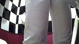 Brunette lovely woman in white pants pisses in the public toilet