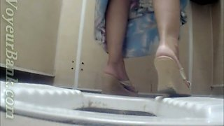 Lovely lady in summer dress pisses in the toilet restroom