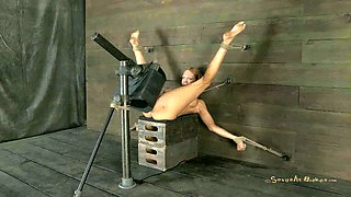 Lying on the wooden boxes all naked blonde is fucked with sex machine