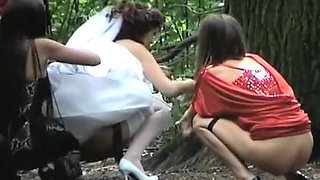 Bride and bride maids peeing outdoors