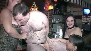Hairy dude lets three insatiable sluts suck his wang in a bar