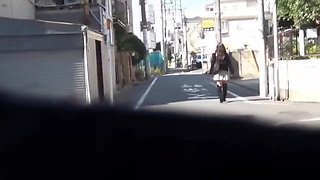 Asian pisses behind car