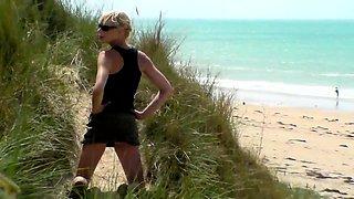 Slender blonde milf gives a wonderful handjob on the beach