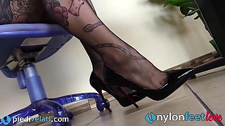 Tattoed secretary in high heels and stockings shows feet