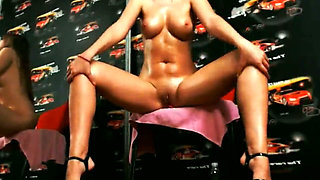 Beautiful naked and oiled chick with huge boobs strips next to a big mirror